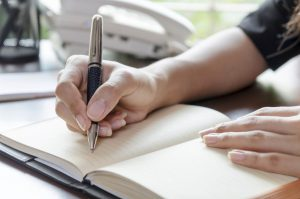 Hand of women who try to write in a notebook