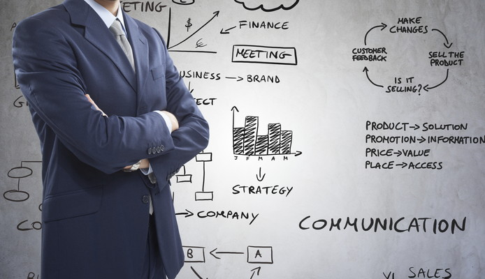 Businessman in front of business related diagrams and charts