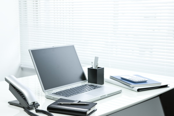 It is put notes and a laptop on top of the white office desk, work landscape