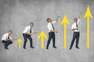 There are four picture men in suits to express the arrow extending above how the happily go extend efforts in a major
