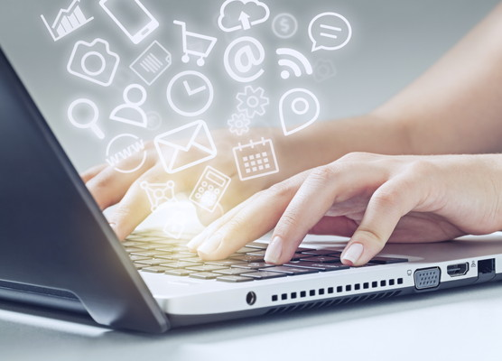 woman typing on laptop and media icons fly off