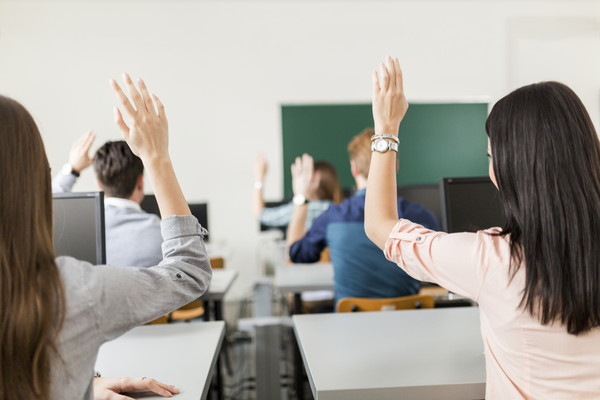 Young students raising hands in a classroom showing they are ready