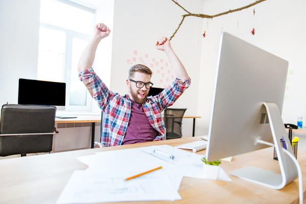 Happy successful man in glasses with raised hands sitting on workplace in office