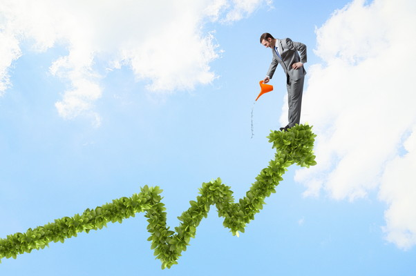 Young cheerful businessman watering green growing graph with can