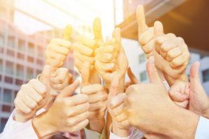Viele Sieger und Gewinner halten zusammen ihre Daumen hoch