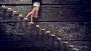 Retro image of a businessman walking his fingers up wooden steps mounted in rustic wooden boards towards light in a conceptual image of personal development, growth and success.