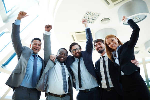 Business team with arms raised and smiling