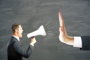 Irritated young businessman with megaphone screaming at hand showing stop gesture on chalkboard background. Protest concept