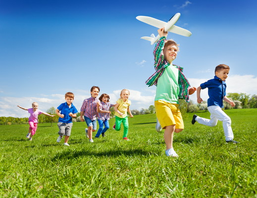 Group of active running kids with boy holding big white airplane toy in the field during summer sunny day