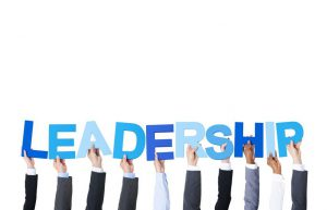 Business People Arms Raised and Holding the Word Leadership