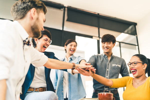 Multiethnic diverse group of happy colleagues join hands together. Creative team, casual business coworker, or college students in project meeting at modern office. Startup or teamwork concept