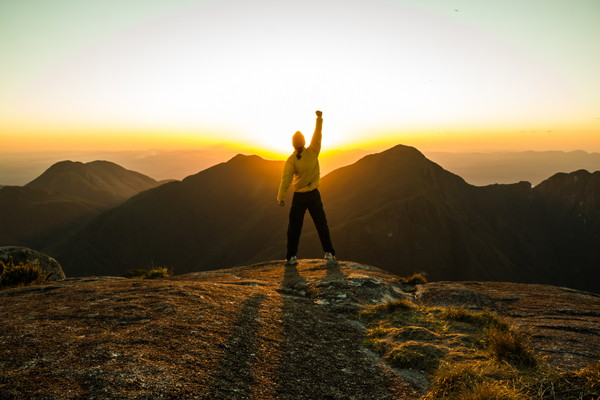 Man celebrating success on top of a mountain with one arm Raised and Hands Closed
