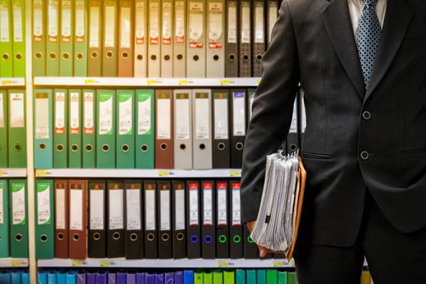 businessman holding data files on binder shelves background