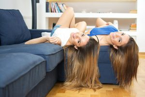 Twin sisters laying upside down on a sofa at home.