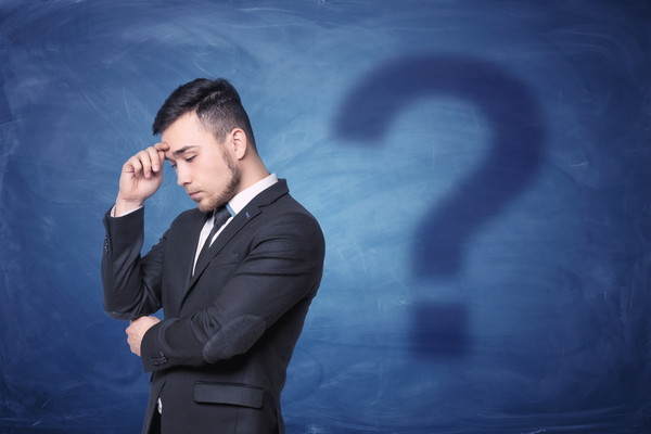 Thoughtful businessman on blue chalkboard background with a shadow question mark behind him. Business and management. Workplace decisions. Problems and solutions.