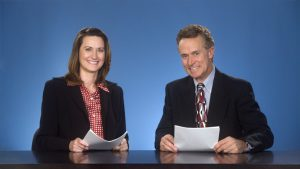 Male and female newcasters sitting at desk smiling at viewer.