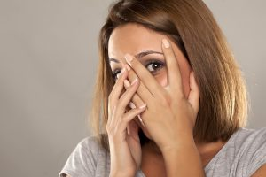 happy young woman covers her face with her hands and peep through her fingers