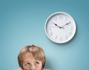 Young boy looking up at a clock concept for deadline, anxiety and stress