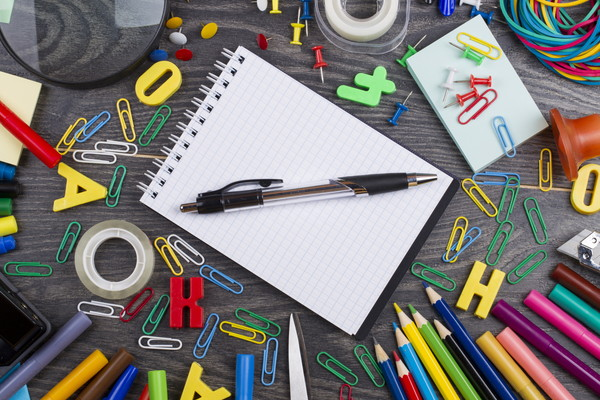 Back to school. Set of school objects for modern education: pens, scissors, pensils and other multicolored accessories on wooden desk. Top view