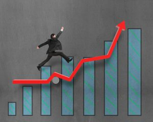 Businessman running and jumping on growth red arrow with chart in concrete wall background