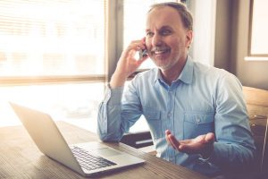 Handsome mature businessman is talking on the mobile phone and smiling while working in office